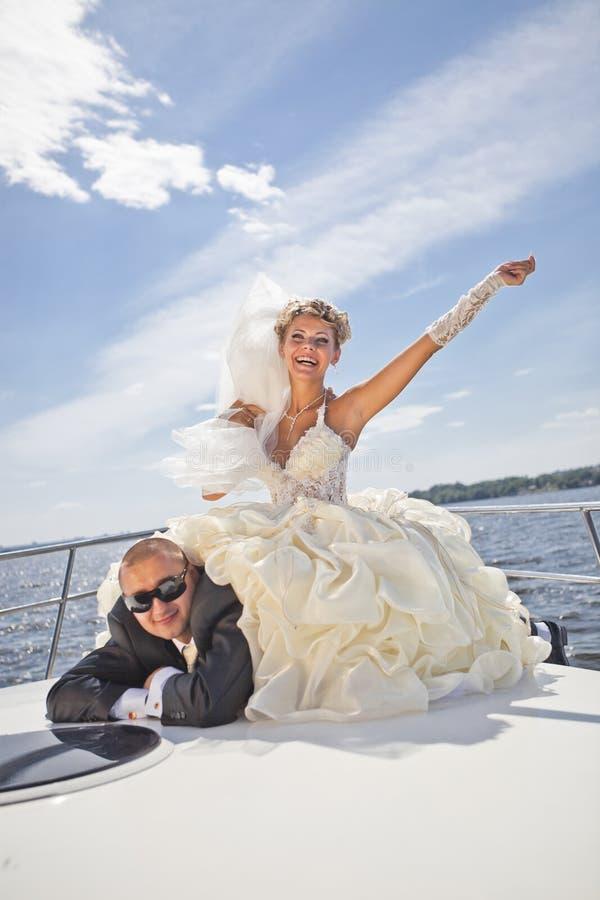 Gelukkige bruidegom en de bruid op het jacht stock fotografie