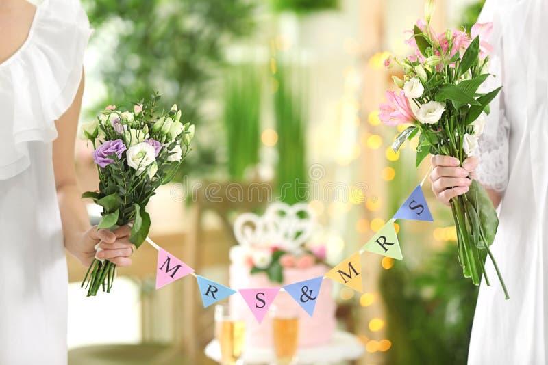 Gelukkige bruiden die boeketten van mooie bloemen en slinger houden stock fotografie