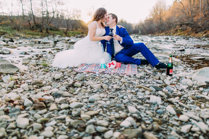 Gelukkige bruids paar het drinken wijn op de rotsachtige bank van de kiezelsteenrivier met bosheuvels en stroom royalty-vrije stock afbeelding