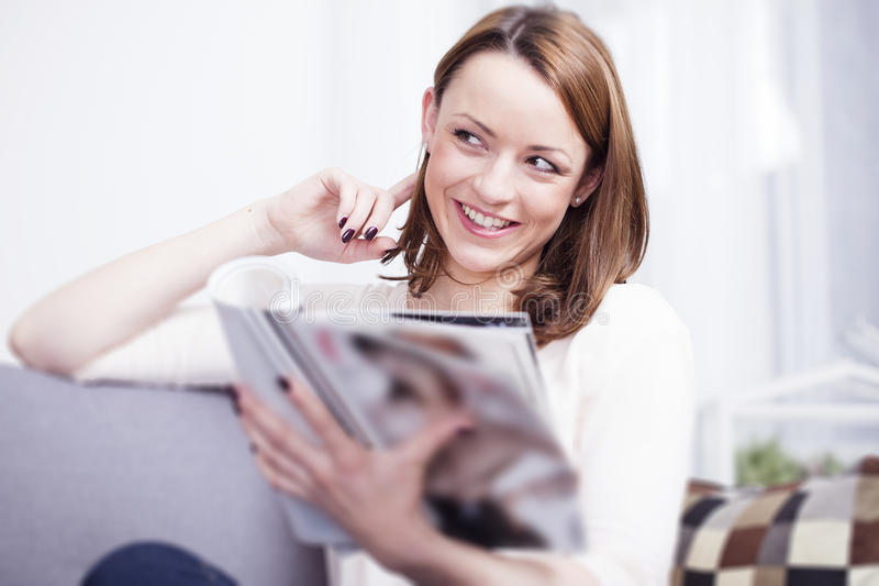 Gelukkige bruine haired meisjeszitting die op een bank glimlachen royalty-vrije stock foto's