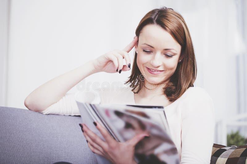 Gelukkige bruine haired meisjeszitting die op een bank glimlachen stock fotografie