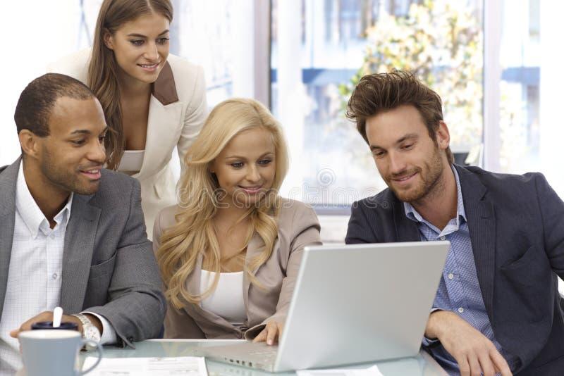 Gelukkige businessteam die met laptop computer werken stock foto's