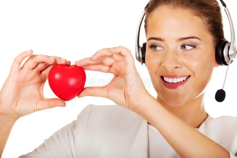 Gelukkige call centrevrouw met hartstuk speelgoed royalty-vrije stock afbeeldingen