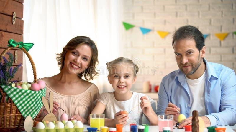 Gelukkige camera onderzoeken en familie die, kleurende eieren, Pasen-voorbereiding glimlachen royalty-vrije stock afbeeldingen