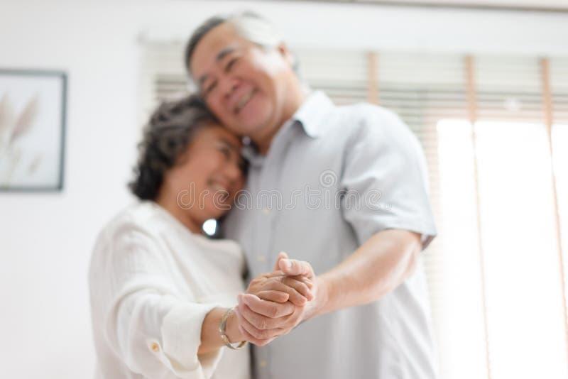 Gelukkige charmante bejaarde Aziatische vrouw die terwijl het dansen met haar echtgenoot in de woonkamer, nadruk op handen glimla stock foto's