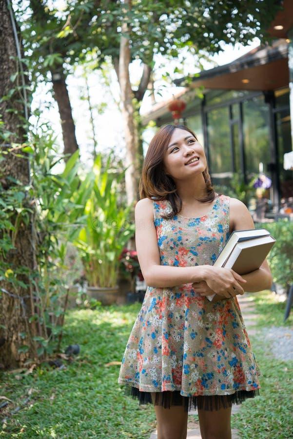 Gelukkige charmante jonge vrouw die en notitieboekjes bevinden houden zich bij hom stock foto's