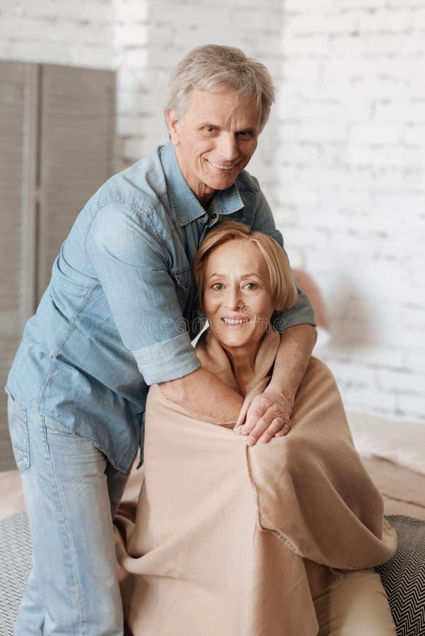 Gelukkige charmante mens die zijn vrouw koesteren stock fotografie