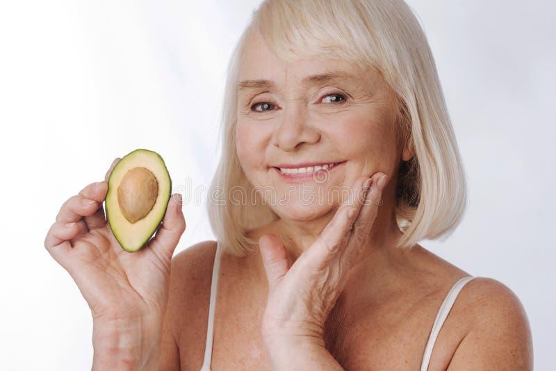 Gelukkige charmante vrouw die zich tegen witte achtergrond met avocado bevinden stock afbeeldingen