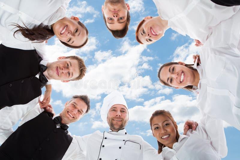 Gelukkige chef-kok en kelners die zich in wirwar tegen hemel bevinden stock foto's