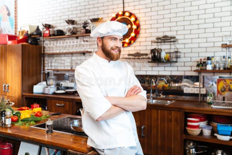 Gelukkige chef-kokkok die zich op de keuken bevinden royalty-vrije stock fotografie