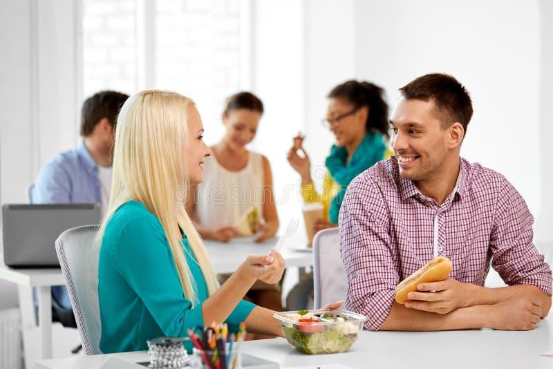 Gelukkige collega's die lunch hebben en op kantoor eten stock afbeeldingen