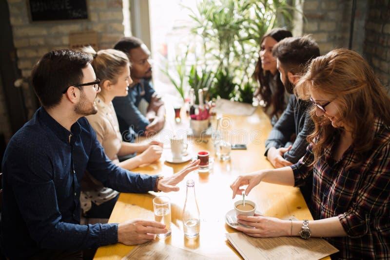Gelukkige collega's die van het werk in restaurant socialiseren royalty-vrije stock foto's