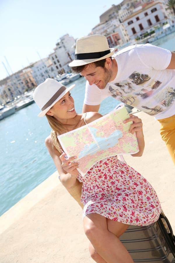 Gelukkige coule van toeristen op vakantie die kaart lezen royalty-vrije stock fotografie