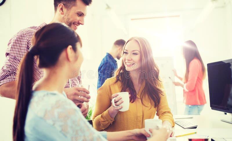 Gelukkige creatieve team het drinken koffie op kantoor stock afbeeldingen