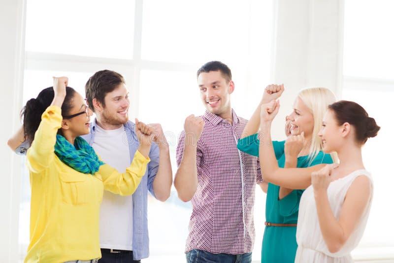 Gelukkige creatieve team het vieren overwinning in bureau stock foto's
