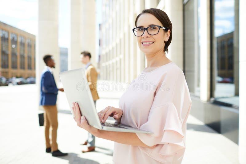 Gelukkige dame die laptop in openlucht met behulp van royalty-vrije stock afbeeldingen