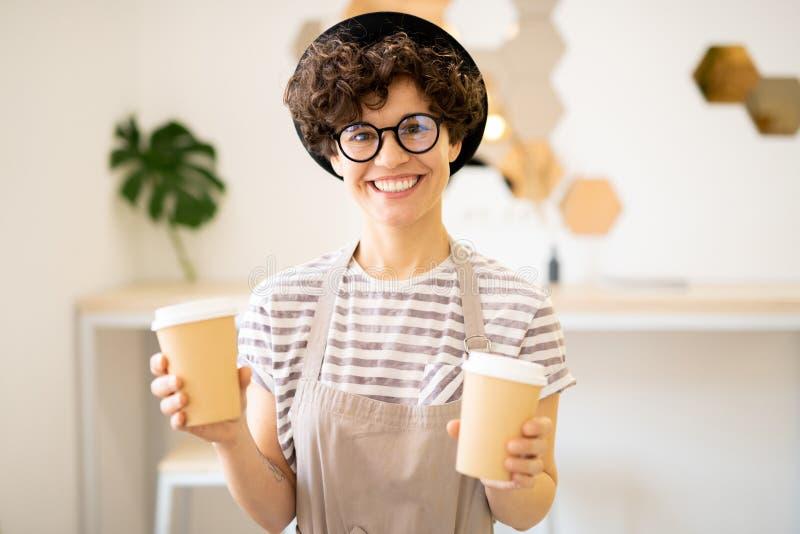 Gelukkige damebarista met beschikbare koffiekoppen royalty-vrije stock fotografie