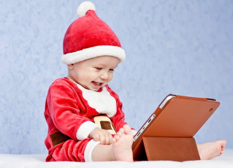 Gelukkige de babyjongen van de santahelper met digitale tablet stock foto's