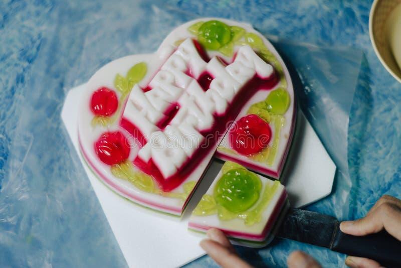 Gelukkige de gelei buitensporige cake van de Verjaardagskokosnoot op de blauwe lijst stock foto's