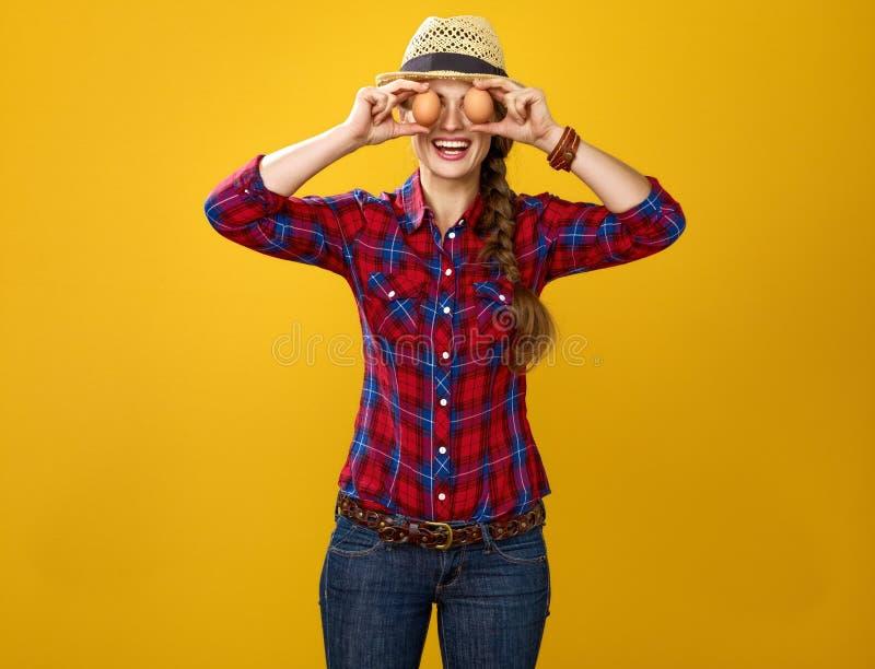 Gelukkige de holdingseieren van de vrouwenkweker voor gezicht zoals ogen stock foto's