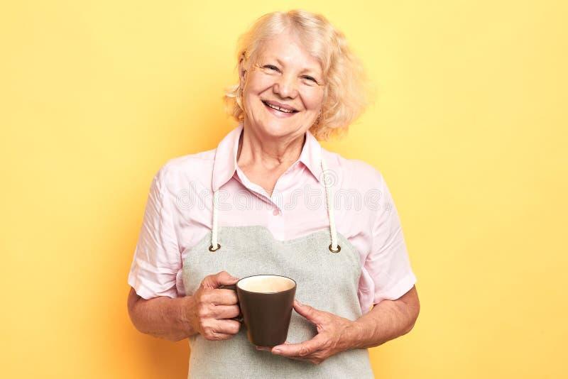 Gelukkige de koffiekop van de grootmoederholding op gele achtergrond royalty-vrije stock foto's