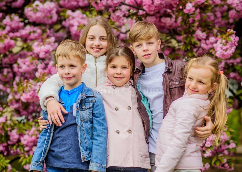 Gelukkige de lentevakantie De kinderen genieten van de warme lente Verloren in bloesem Meisjes en jongensvrienden die dichtbij sa royalty-vrije stock fotografie