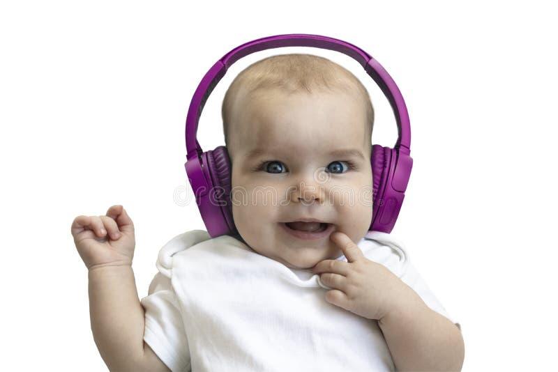 Gelukkige de Peuter van het babykind glimlachend in draadloze purpere hoofdtelefoons op een witte achtergrond Het concept technol stock fotografie