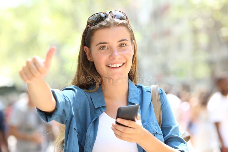Gelukkige de telefoon gesturing duim van de tienerholding omhoog royalty-vrije stock foto's