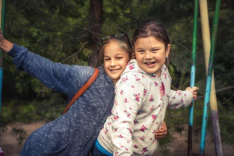 Gelukkige de vriendenpret die van kinderenmeisjes samen slingerende de vriendschapssamenhorigheid omhelzen van conceptenkinderjar stock foto's