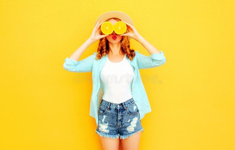 Gelukkige de vrouwenholding van het de zomerportret in haar handenplakken die van sinaasappel haar ogen in strohoed, borrels op k royalty-vrije stock afbeeldingen