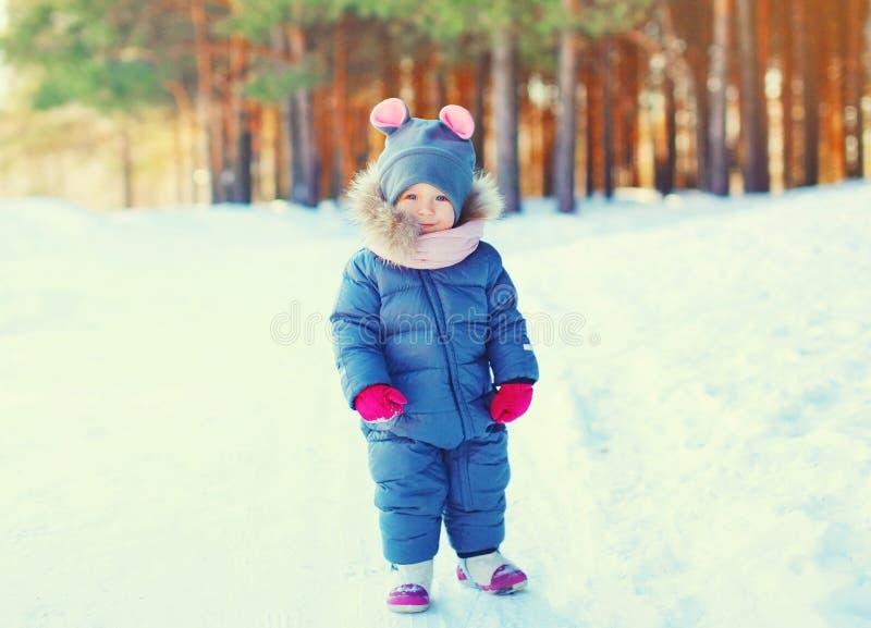 Gelukkige de winter weinig glimlachend kind die in sneeuw lopen stock foto's