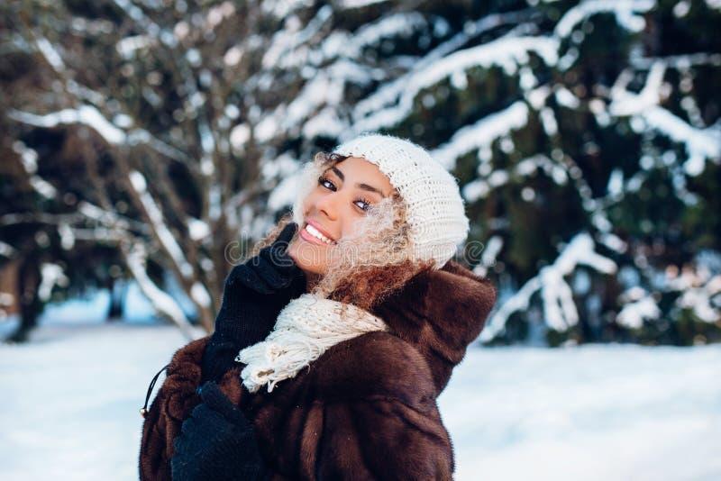 Gelukkige de winterogenblikken van blije jonge vrouw met afrohaar, witte de winterkleren die pret op straat in sneeuwende tijd he stock afbeeldingen