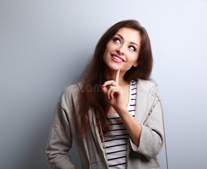 Gelukkige denkende vrouw die in vrijetijdskleding omhoog kijken royalty-vrije stock fotografie