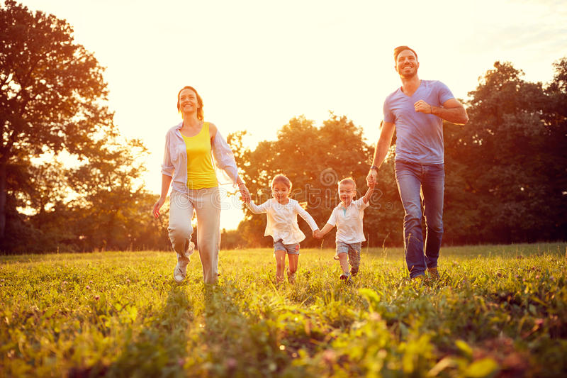 Gelukkige die familie op groen gebied in werking wordt gesteld royalty-vrije stock afbeelding