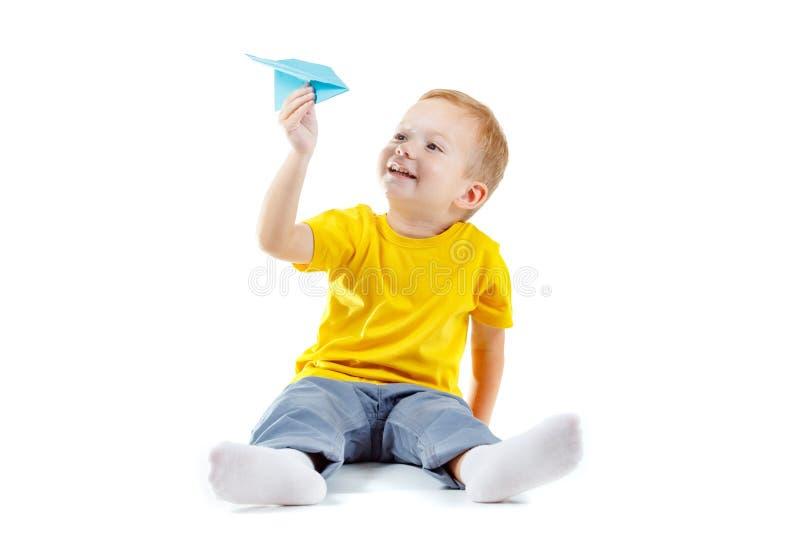 Gelukkige die jongen met document vliegtuig op wit, persoon wordt geïsoleerd Gelukkige die jongen met document vliegtuig op wit,  royalty-vrije stock fotografie