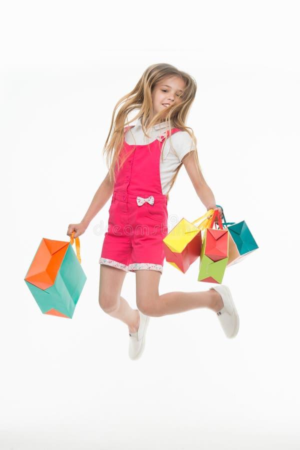Gelukkige die kindsprong met het winkelen zakken op wit wordt geïsoleerd Meisjeglimlach met document zakken Jong geitjeklant op m stock foto