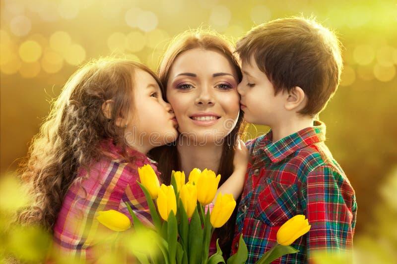 Gelukkige die moeder door haar dochter en zoon wordt gekust royalty-vrije stock foto's