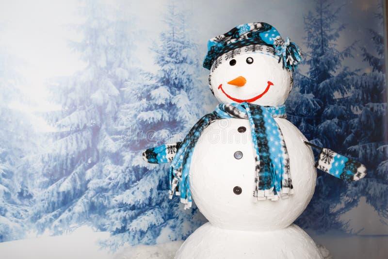 Gelukkige die sneeuwman door de winterlandschap wordt omringd met dalende sneeuw royalty-vrije stock afbeeldingen
