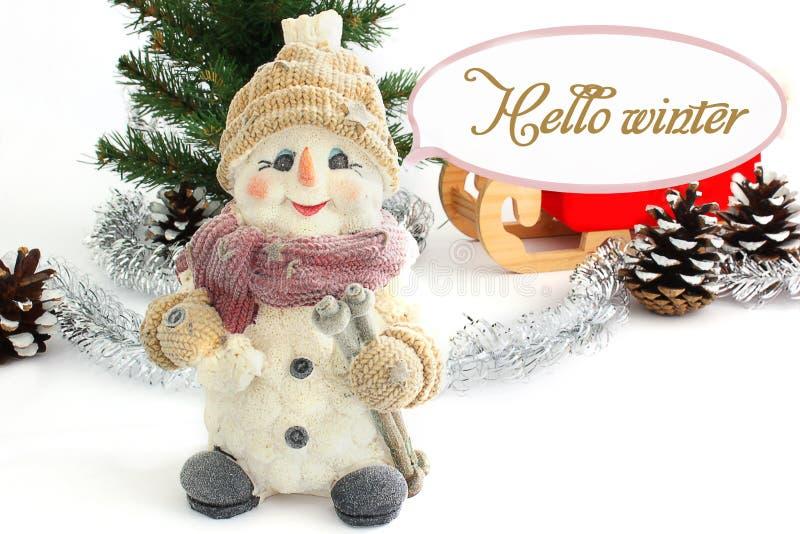 Gelukkige die Sneeuwman door denneappels wordt omringd Sneeuwman met de ar van de Kerstman stock afbeelding