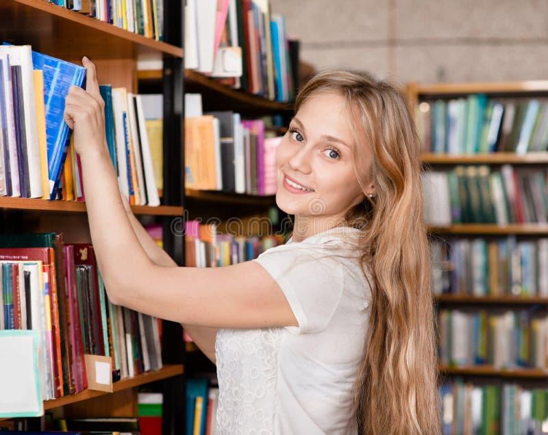 Gelukkige die student in de bibliotheek door boeken wordt omringd royalty-vrije stock fotografie