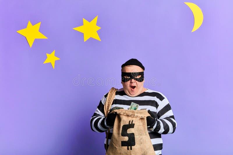 Gelukkige dief in masker en handschoenen die een zak geld openen stock afbeeldingen