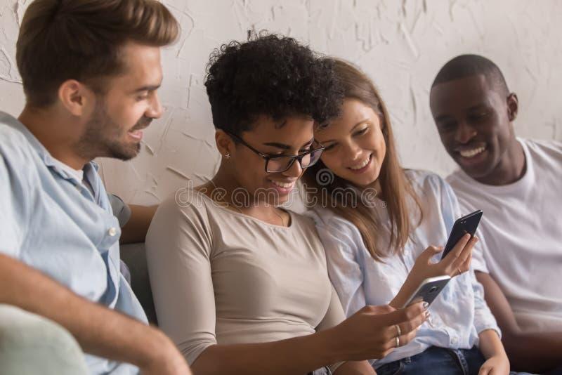 Gelukkige diverse jongeren die sociale media apps op telefoons gebruiken stock afbeeldingen