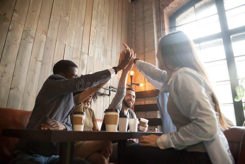 Gelukkige diverse vrienden die hoogte vijf geven die uit in koffie koelen stock fotografie