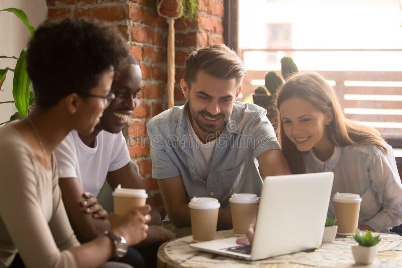 Gelukkige diverse vriendengroep die laptop het letten op komediefilm bekijken stock afbeelding