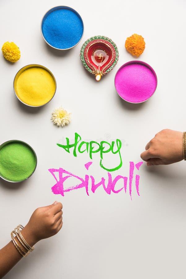 Gelukkige Diwali-Groetkaart die kleurrijke Rangoli in kommen, diya of kleilamp en gelukkige diwali gebruiken die met bloemen schr stock afbeeldingen