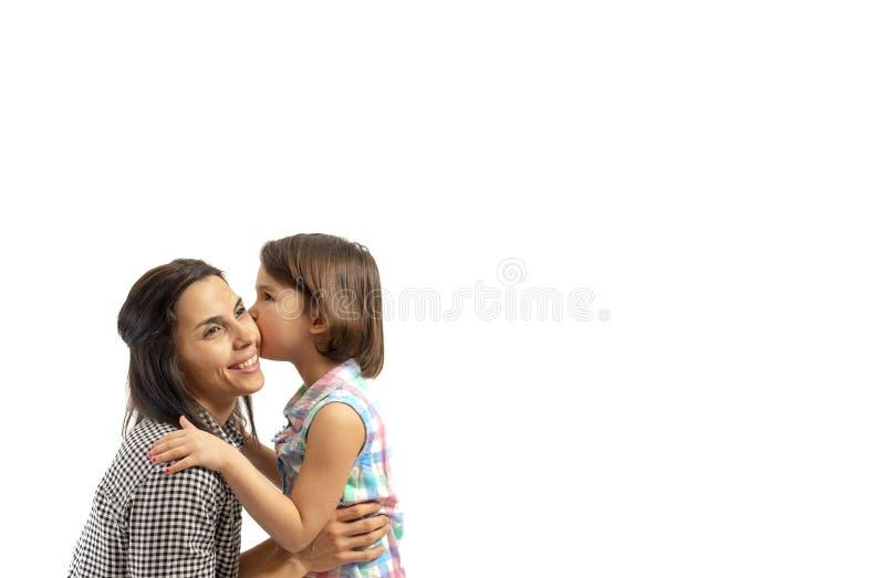 Gelukkige dochter die haar die moeder kussen, op witte achtergrond wordt geïsoleerd royalty-vrije stock foto's