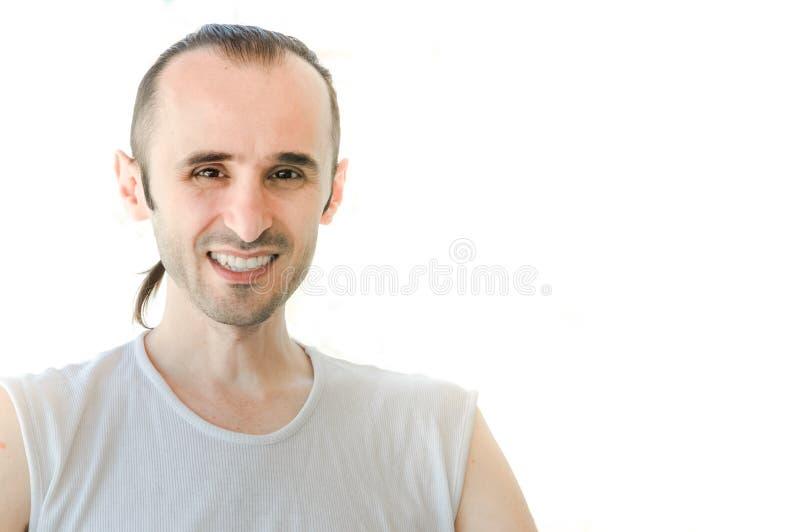 Gelukkige donkerbruine mens die met wit overhemd op witte achtergrond glimlachen stock afbeelding