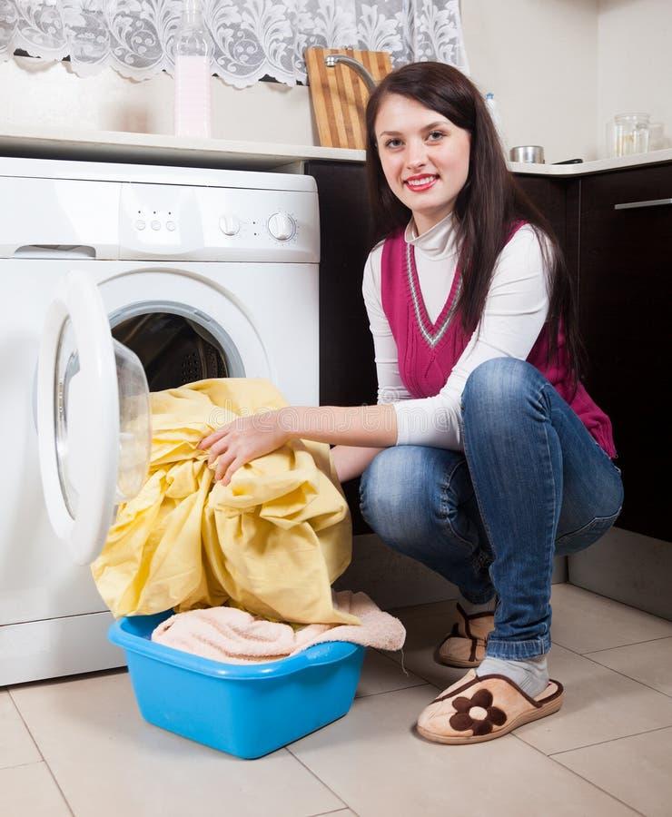 Gelukkige donkerbruine vrouw die wasserij doen stock fotografie