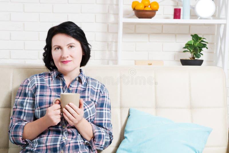 Gelukkige donkerbruine vrouw in een comfortabele zitting van het huismilieu op bank royalty-vrije stock fotografie
