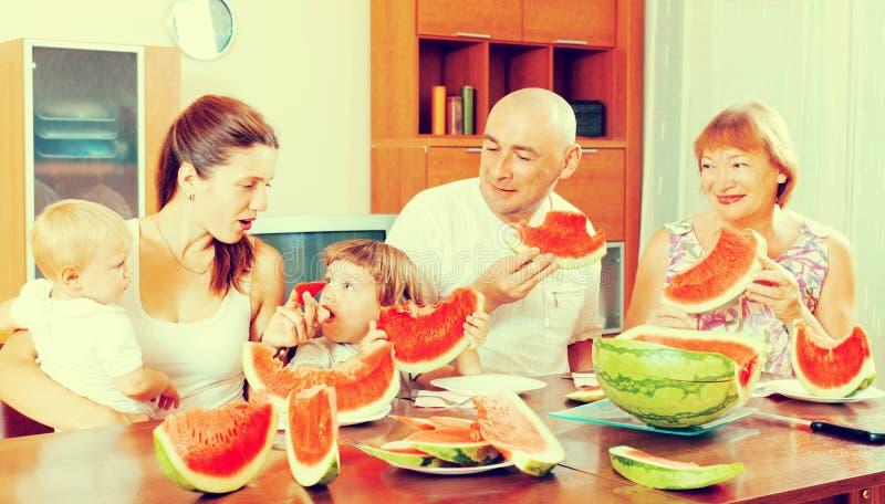Gelukkige drie generatiesfamilie die watermeloen over lijst eten royalty-vrije stock fotografie